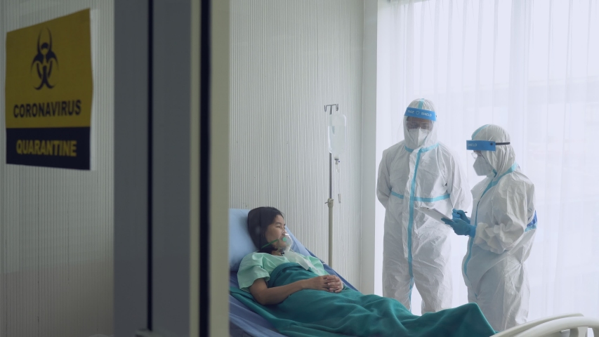 doctor and nurse in personal protective equipment or ppe treating the patient who had pneumonia from covid-19 or coronavirus infection in isolation room in hospital. medical concept Royalty-Free Stock Footage #1051201168