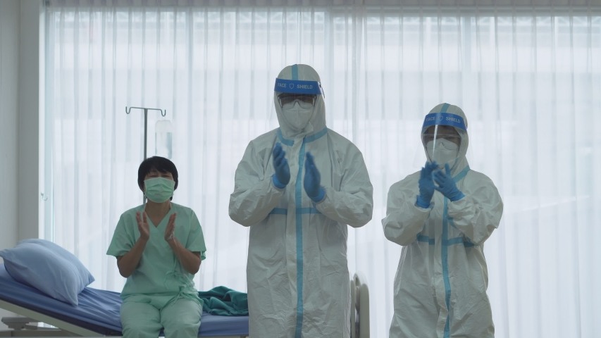 Asian doctor and nurse in personal protective equipment or ppe with senior patient clapping hands to support medial staff who fight covid-19 or coronavirus infection in hospital Royalty-Free Stock Footage #1051201204