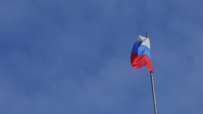 The developing flag of the Russian Federation standing on a flagpole against a blue sky. #1051201666