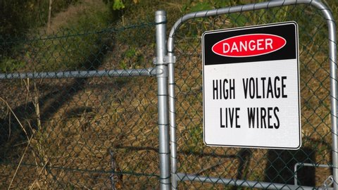 High Voltage Live Wires sign outside of train track line