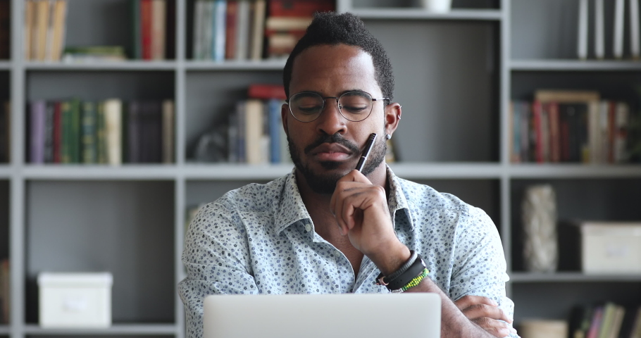 Head shot pensive young biracial man looking at laptop screen, thinking of hard problem decision or case study. Thoughtful mixed race entrepreneur businessman employee stack with difficult task. Royalty-Free Stock Footage #1051226896