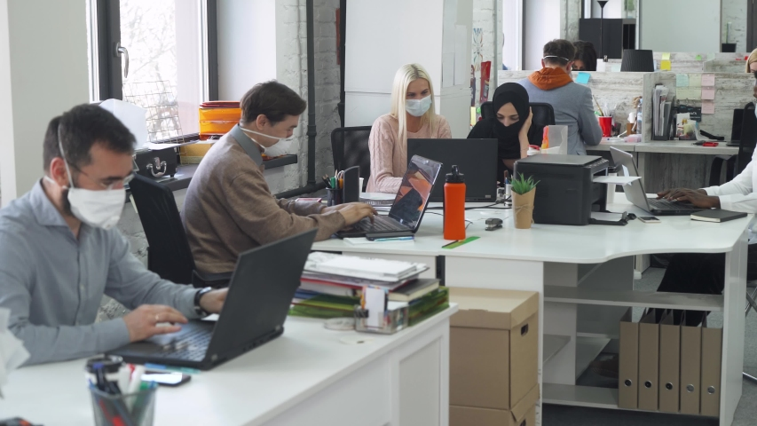 Modern international office, working and communicate in an open space, office workers and managers in medical masks working at computers, protection from the virus, working during the pandemic. | Shutterstock HD Video #1051228531
