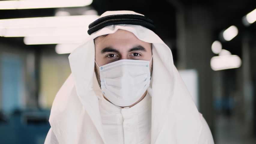 Arab businessman in kandura takes off medical mask. Male breathes deeply and smiling looking at camera. Medical concept. Close up portrait . 4k | Shutterstock HD Video #1051231063