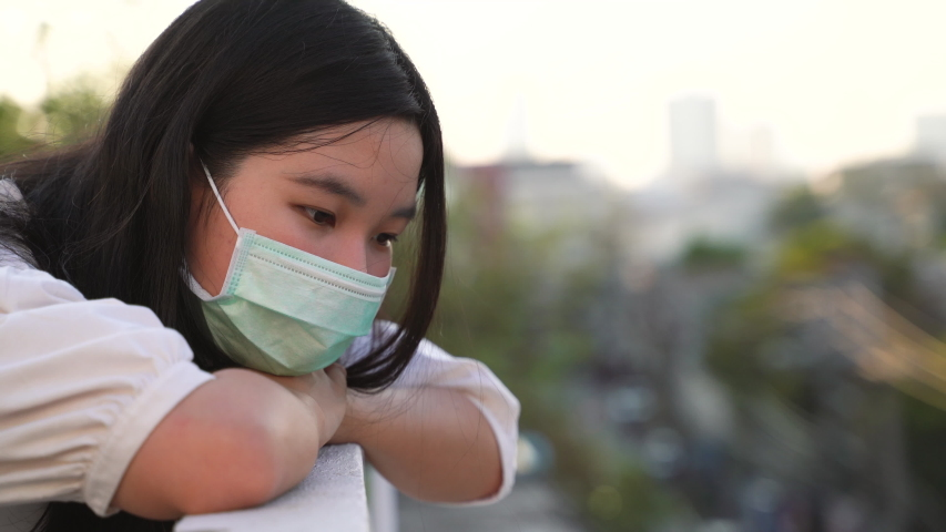 Young asian millennial gen z woman standing at rooftop feeling bored and looking at cityscape while wearing mask, self quarantine or stay at home during COVID-19 and coronavirus pandemic | Shutterstock HD Video #1051233067