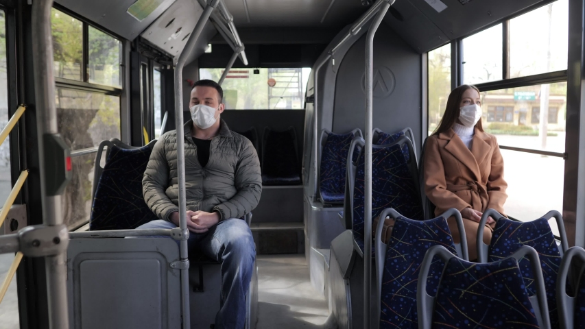 Young man and woman with protective mask traveling in the public transport by bus Royalty-Free Stock Footage #1051246201