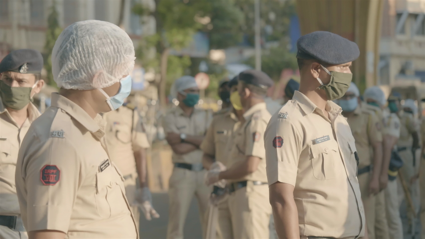 On duty Policemen/ police force/ constables in uniform standing on the road wearing proactive face mask during city lockdown amid coronavirus/ covid19 epidemic/ pandemic in Mumbai, India (April 2020)