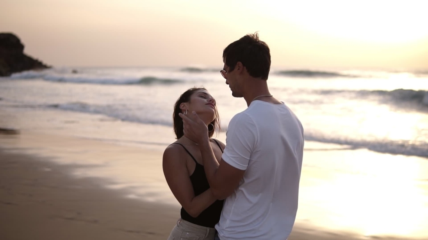 Young couple kissing and bonding at sunset on beach. Loving man and woman hugging in bright rays of sun on background of the lake. Passioned guy and girl in love