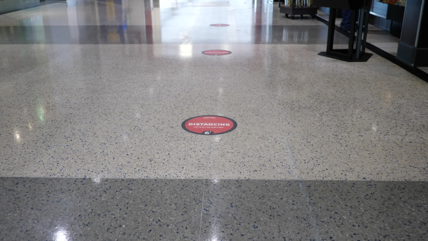 """Social distancing stickers """"Let's all do our part"""" spaced 6 feet apart on a shiny floor at the airport to help customers queue safely"""