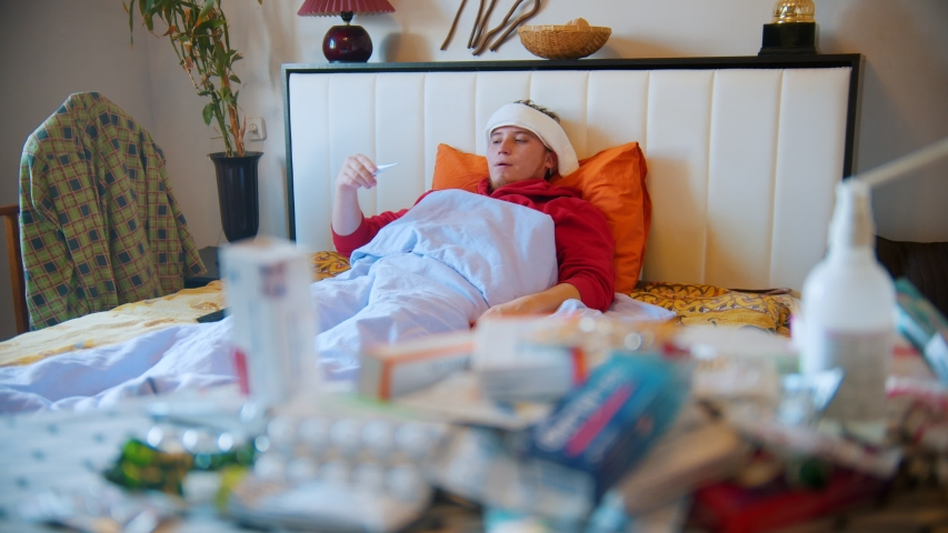 A young sick man lying in the bed and measures the temperature with thermometer | Shutterstock HD Video #1051269172