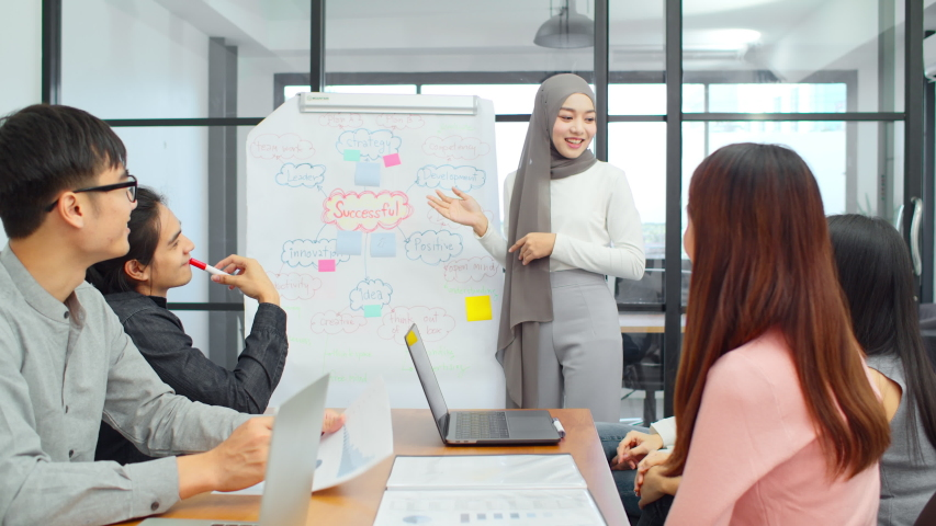 Asian muslim woman lead group of young Asian business creative team in brainstorm meeting presentation. Girl power, colleague coworker partnership teamwork, people cooperation, or idea sharing concept