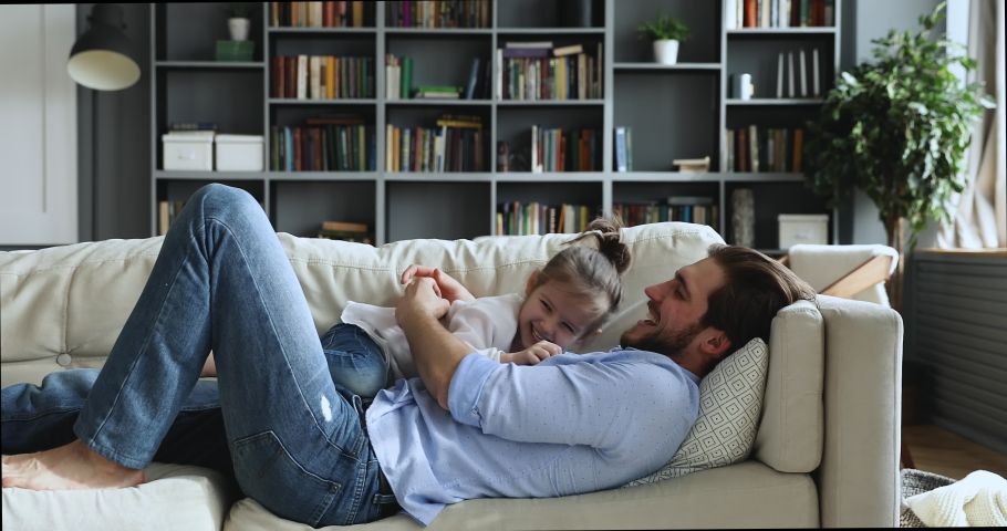 Happy family cute preschool daughter and dad having fun tickling laughing lying on sofa together. Carefree young adult father playing with small child girl at home enjoy funny game in living room. Royalty-Free Stock Footage #1051271800