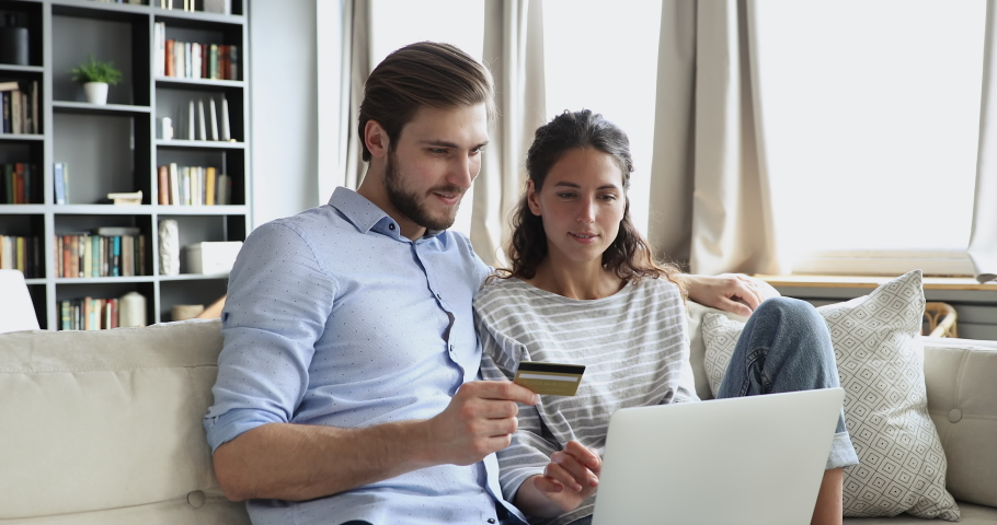 Happy young couple customers holding credit card buy products or services online using laptop. Smiling husband and wife shoppers pay doing shopping on website making e commerce secure digital payment. Royalty-Free Stock Footage #1051271869