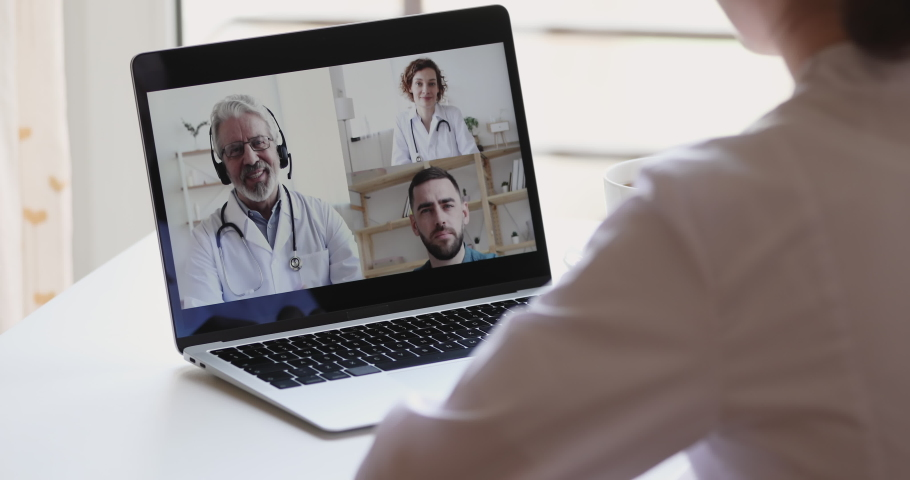 Female medical worker participate online webcam conference on laptop screen. Doctors group discuss healthcare during medic group video call virtual training webinar concept. Over shoulder closeup view