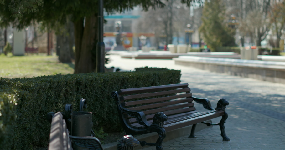 Empty park alley in city. Pan right view of empty benches and paved alley on sunny day in city during COVID 19 quarantine | Shutterstock HD Video #1051284928