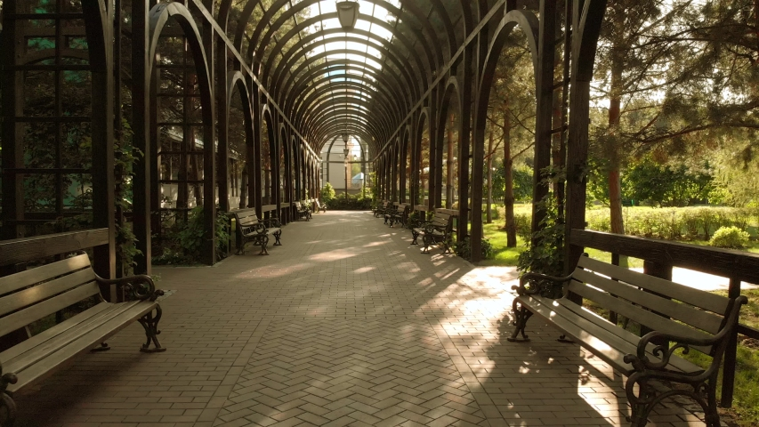 Tunnel archway in a park. Cobblestone floor. Row of benches. Royalty-Free Stock Footage #1051288588