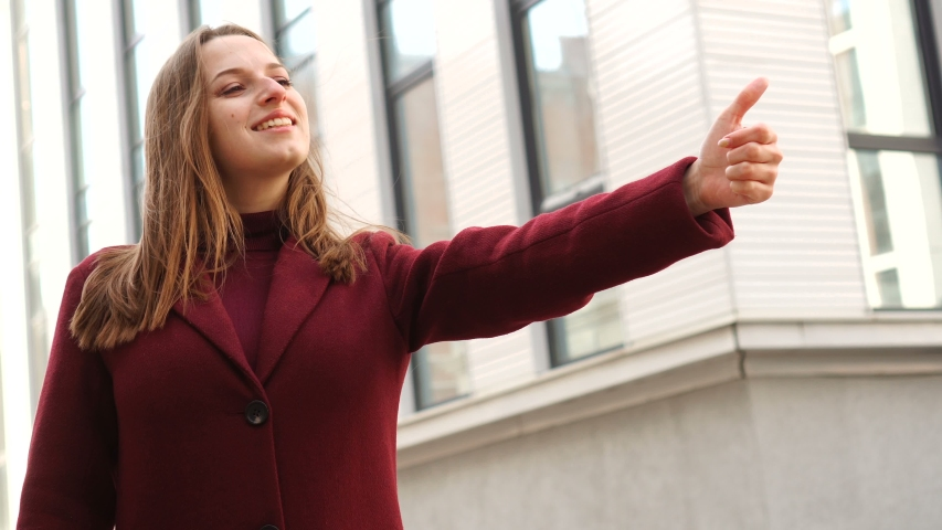 Happy young woman showing like with finger on city street background. | Shutterstock HD Video #1051291258