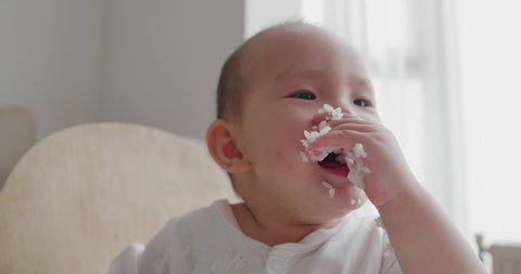 Close up 4k footage of lovely asian baby girl eating steam rice at home adorable kids with food infant learning to eat by herself