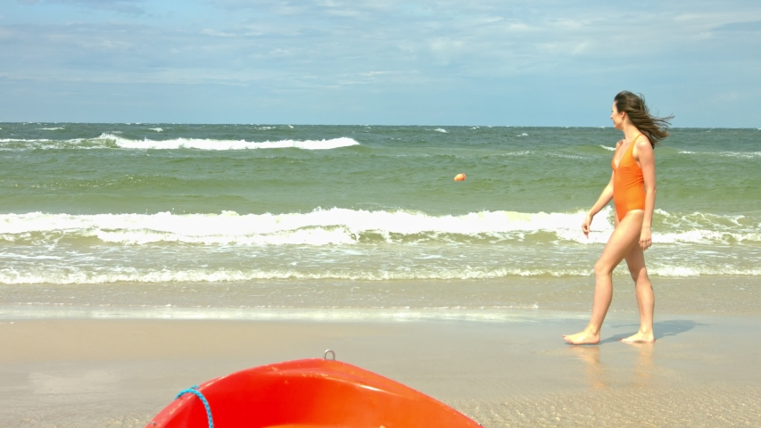 Girl in orange one-piece bathe suit at beautiful beach looking out across the water at the crashing waves while on holidays   Shutterstock HD Video #1051294447