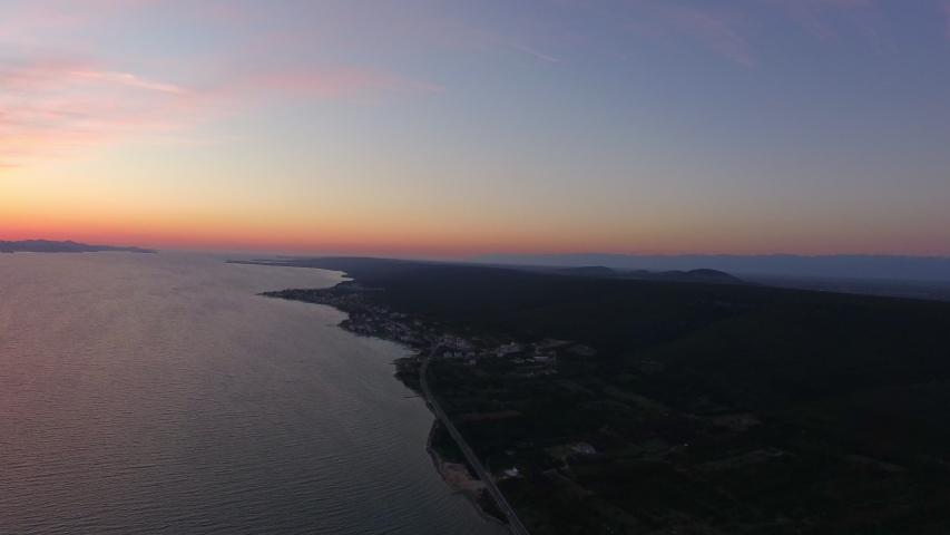 Aerial shot of vehicles on road by sea against sky during sunset, drone descending over landscape - Heart Island, Croatia   Shutterstock HD Video #1051302532
