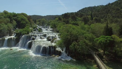Aerial shot of beautiful waterfall in forest, drone is descending over river - Krka, Croatia