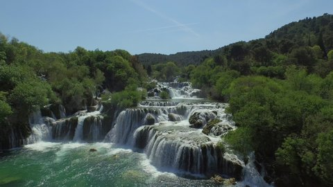 Aerial shot of scenic waterfall in forest on sunny day, drone is descending over river - Krka, Croatia