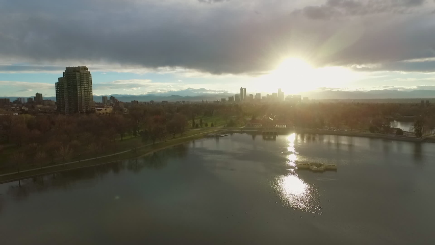 Aerial: Drone reversing from Ferril Lake with reflection of sun in Denver city against sky during sunset | Shutterstock HD Video #1051317073
