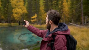 30s Forest Hiker Photographer Man in Woods Shooting Lake View Back Shot Concept. Contemporary Travel Guy Videographer Standing in Nature Scenic and Natural Filming via Panoramic Hold Smartphone Camera