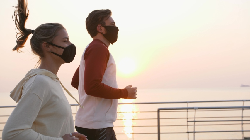 Young fit couple in protective masks running outdoors near the sea during beautiful sunrise, slow motion | Shutterstock HD Video #1051325896