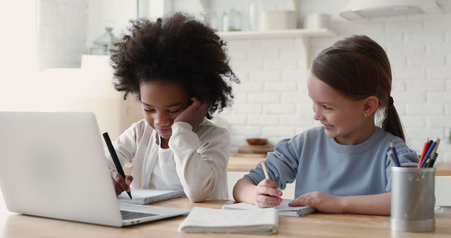 Cute primary school age girls of mixed race ethnicity studying together. African and caucasian sisters or friends doing homework writing exercise distance learning. Diverse children home education. Royalty-Free Stock Footage #1051329862