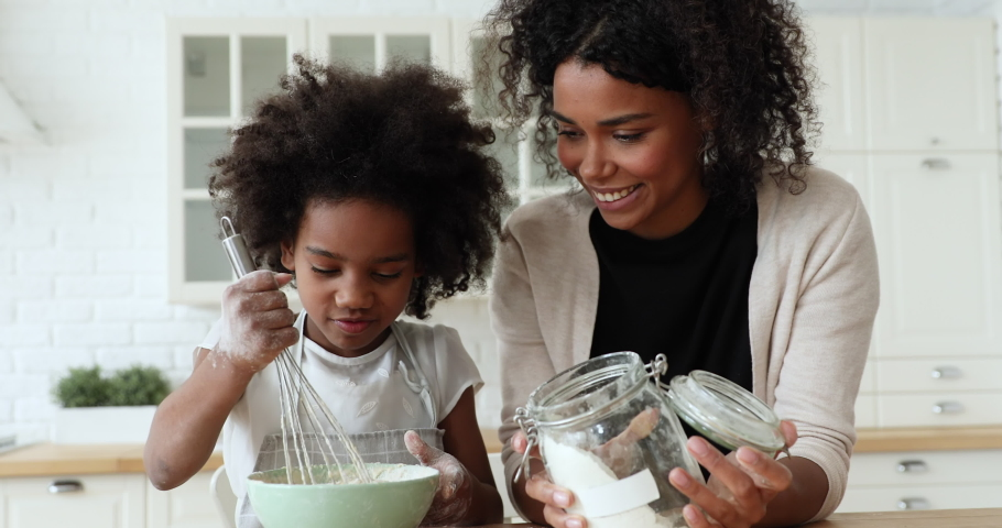 African mom and small kid daughter cooking together making dough in bowl in kitchen. Happy mixed race family prepare cake mix ingredients for pie having fun baking pastry on holiday morning at home.