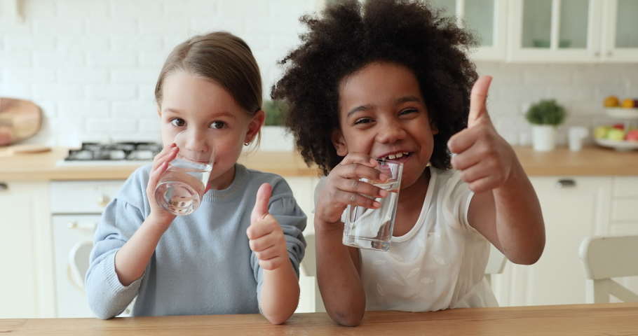 Two funny adorable mixed race children girls holding glasses drinking tasty clean pure mineral water showing thumbs up looking at camera, recommend daily children healthcare morning hydration concept.
