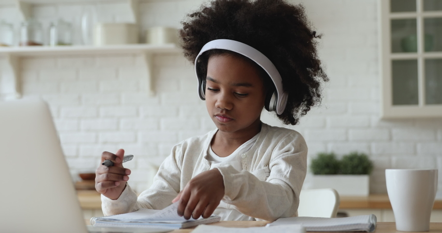 Afro american kid girl school pupil wearing headphones studying online from home watching web class lesson or listening tutor by video call elearning on pandemic isolation. Children remote education. #1051329937