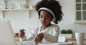 Afro american kid girl school pupil wearing headphones studying online from home watching web class lesson or listening tutor by video call elearning on pandemic isolation. Children remote education.