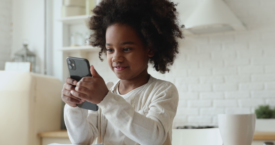 Cute african kid girl holding smart phone enjoying using mobile apps, playing games at home. Small mixed race child learning in cellphone, watching video, having fun with mobile technology concept. Royalty-Free Stock Footage #1051329961