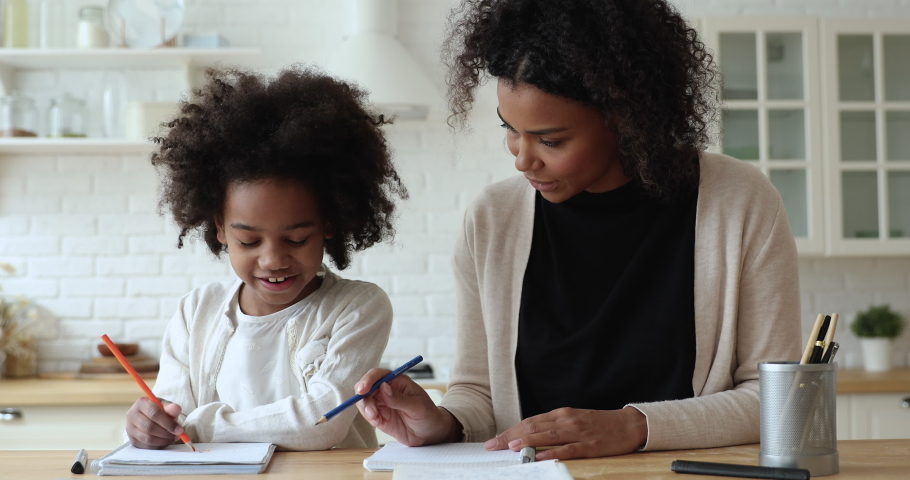 Happy african mum and kid daughter drawing pencils at home. Cute mixed race school child girl playing with young mom, babysitter enjoying creative education activity concept sitting at kitchen table.