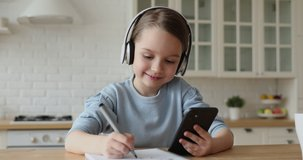 Cute child girl wearing headphones studying online in mobile app by video call with remote teacher, tutor. School kid holding phone doing homework using application, watching class learning at home.