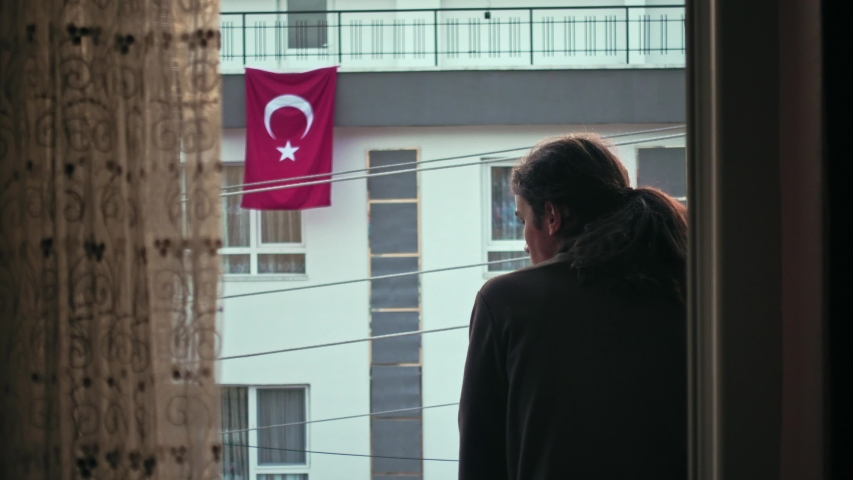 Worried millennial teen with long hair watching the empty street with Turkish flag on the background | Shutterstock HD Video #1051336900