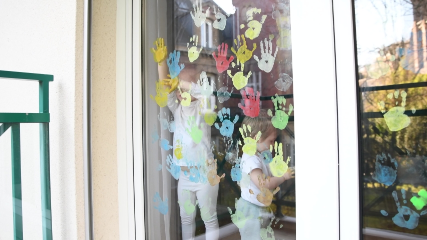 The kids paint with palms on the window. Quarantine | Shutterstock HD Video #1051347403