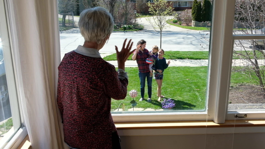 Family waving at grandmother inside during quarantine | Shutterstock HD Video #1051354456
