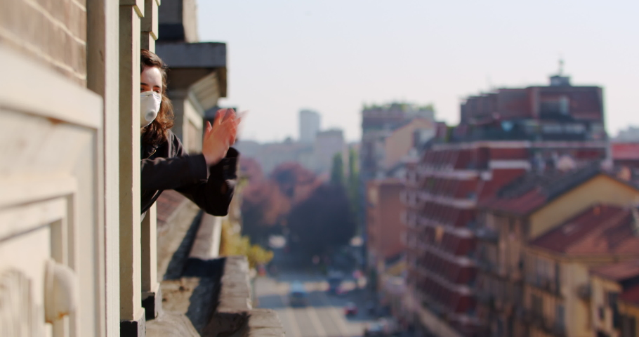 Girl applauds doctors during the coronavirus pandemic in Europe. People look out the window. Quarantine all over the world, a woman sits at home | Shutterstock HD Video #1051356292