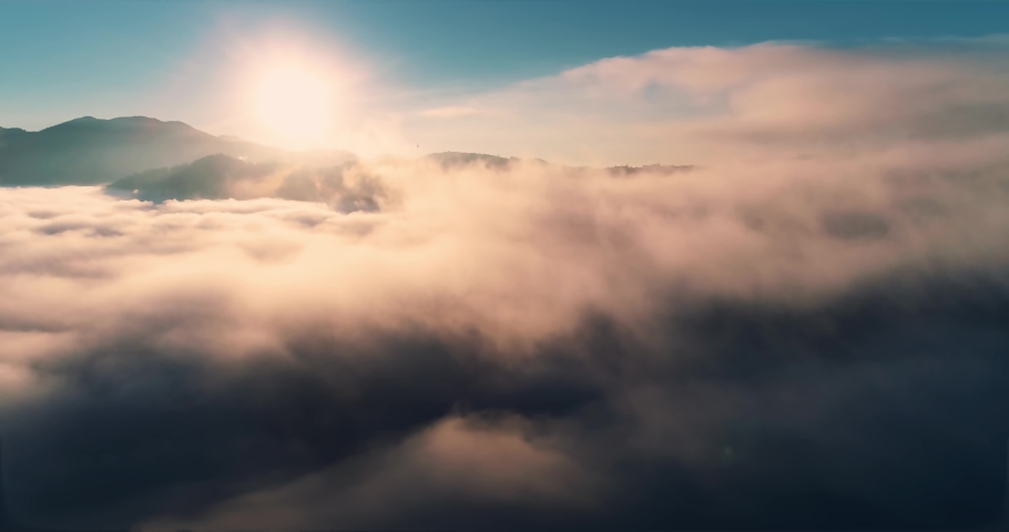 Flying over the clouds during morning sunrise in Carpathian Mountains. Above.Golden fluffy clouds moving softly on the sky and the sun shining through the clouds with beautiful rays and lens flare. Royalty-Free Stock Footage #1051359313