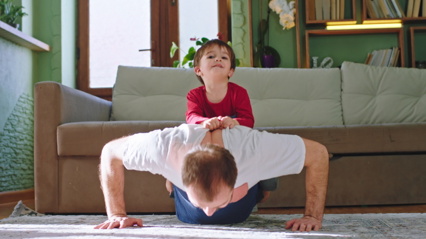 Good time at home father with his small kid doing sport on the carpet in the living room little boy sitting on his dad back while the dad doing push-ups | Shutterstock HD Video #1051374271