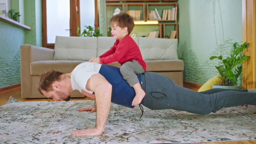 Sport time at home in the living room dad with his small cute son doing push-ups together while the small boy are on his back | Shutterstock HD Video #1051374280
