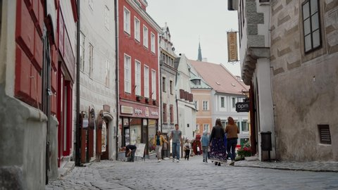 CESKY KRUMLOV, CZECH - MAY 27, 2019: Loving couple of tourists walks along narrow street in old romantic town of Czech Republic. Cozy European street with shop and typical buildings