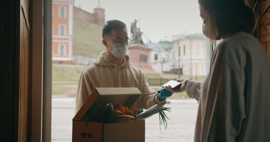 Postman or delivery asian man carry small box deliver to young woman customer at home contactless nfc terminal payment. Man wearing mask prevent covid or coranavirus quarantine pandemic.  | Shutterstock HD Video #1051381360