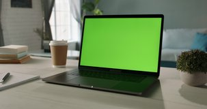 The table of distant worker at home. Modern laptop computer with chroma key green screen. Remote work, distance learning, technology concept close up 4k video template