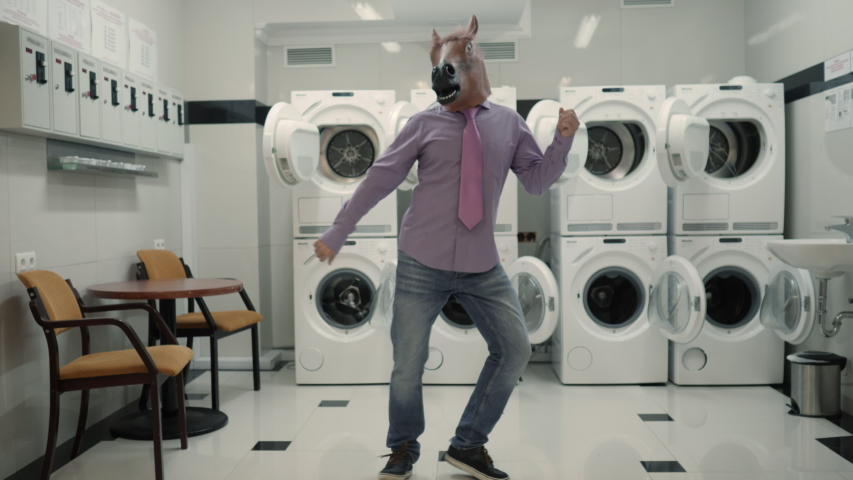Joyful Man in mask horse Dancing Cheerful In Laundry Room. Man Dancing Viral Dance And Have Fun In Laundry Room. Happy Guy Enjoying Dance, Having Fun Together, Party Halloween. Slow Motion. Halloween | Shutterstock HD Video #1051395712