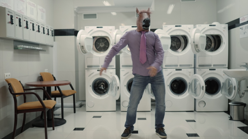 Joyful Man in mask horse Dancing Cheerful In Laundry Room. Man Dancing Viral Dance And Have Fun In Laundry Room. Happy Guy Enjoying Dance, Having Fun Together, Party Halloween. Slow Motion. Halloween | Shutterstock HD Video #1051395721