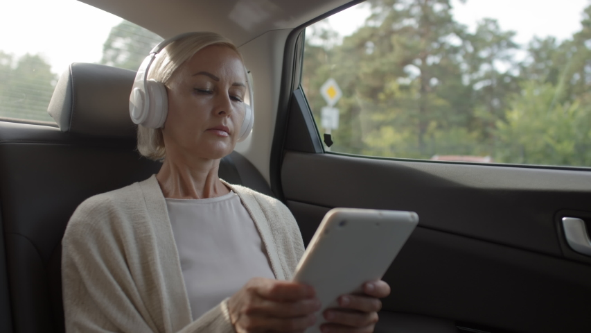Beautiful middle aged woman sitting in backseat of car, typing on digital tablet and listening to music with headphones during ride