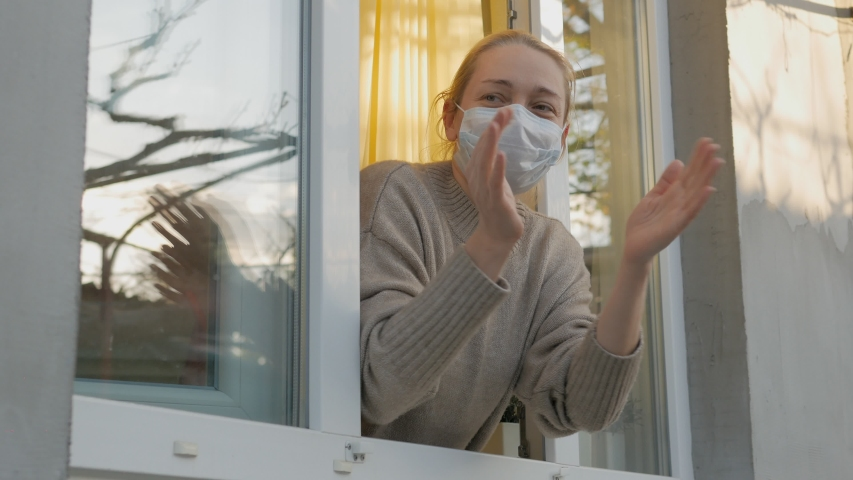 Woman in medical mask claps his hands looking out the open window | Shutterstock HD Video #1051423252